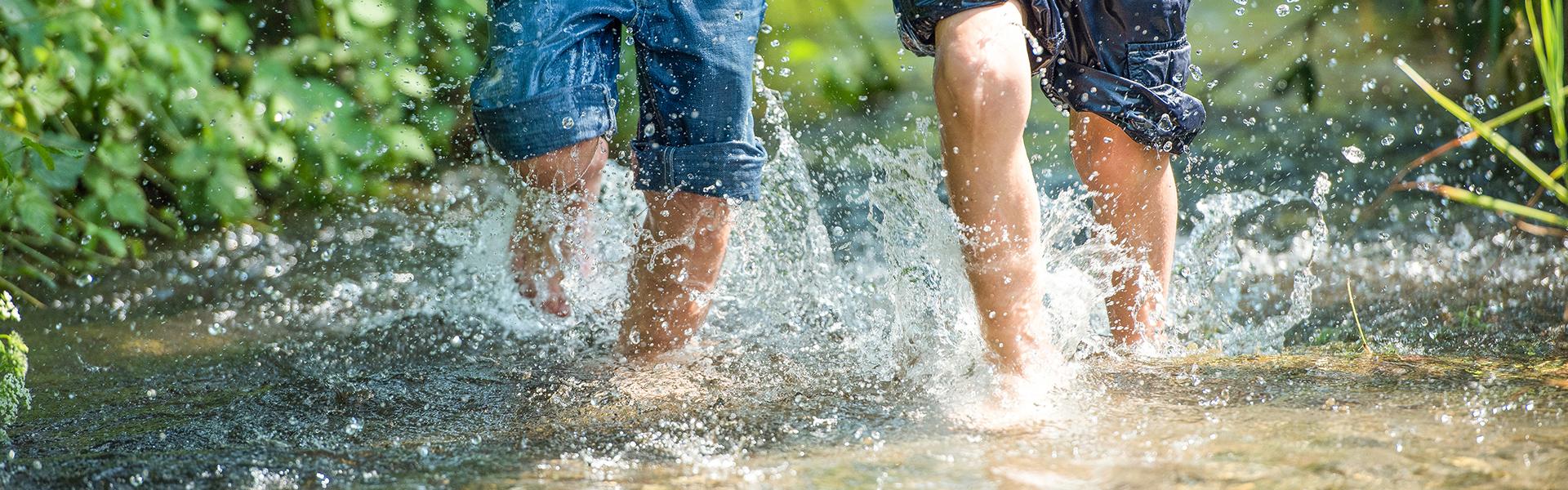 Kinder rennen durch klares Wasser eines Bachs